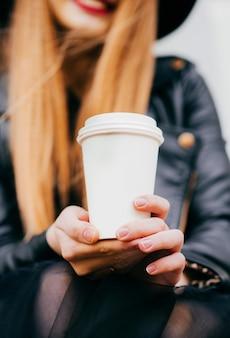 Schönes mädchen, das ein glas mit kaffee anhält
