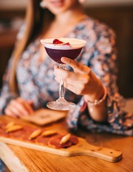 Schönes mädchen, das einen exquisiten burgunderroten cocktail in einem speziellen glas an der bar und mit snacks hält