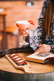 Schönes mädchen, das einen exquisiten cremigen cocktail in einem speziellen glas an der bar hält, sitzt auf einem tisch in form eines holzfasses