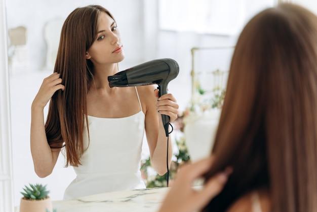 Schönes mädchen, das einen haartrockner benutzt und beim betrachten des spiegels lächelt. lächelnde frau, die haare mit haartrockenmaschine trocknet. glückliches mädchen, das den spiegel anschaut, während es einen haartrockner im badezimmer benutzt