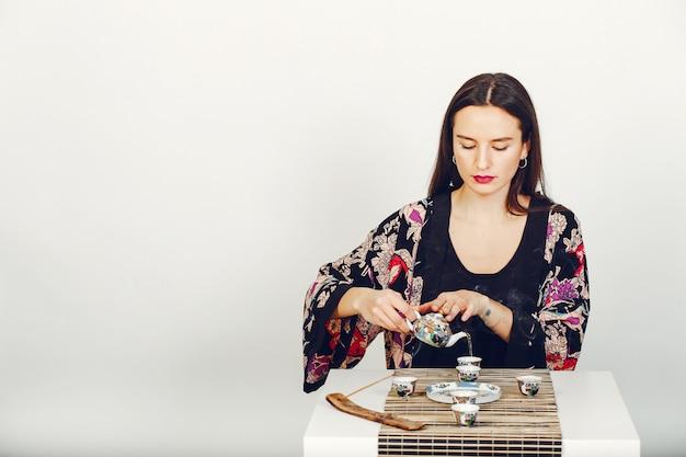 Schönes mädchen, das einen tee in einem studio trinkt