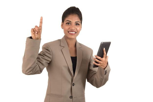Schönes mädchen, das etwas in der hand mit smartphone oder tablette hält und präsentiert