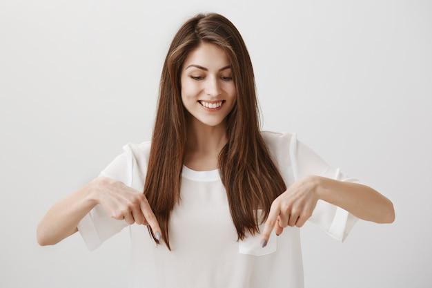 Schönes mädchen, das finger nach unten zeigt, um ankündigung zu zeigen, glücklich lächelnd