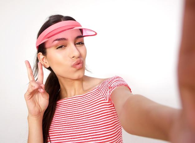 Schönes mädchen, das für selfie mit friedenshandzeichen aufwirft