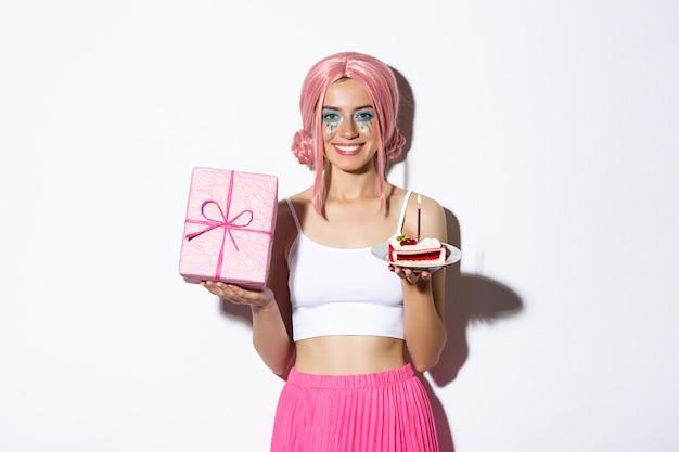 Schönes mädchen, das geburtstag in rosa perücke feiert, geschenk und b-tages-kuchen haltend hält.