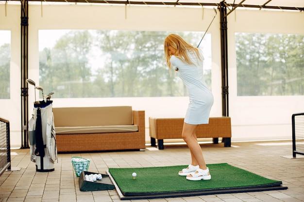 Schönes mädchen, das golf auf einem golfplatz spielt
