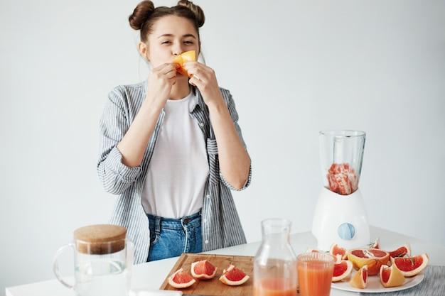 Schönes mädchen, das grapefruitstück über weißer wand isst. gesunde fitnessernährung. speicherplatz kopieren.