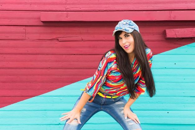Schönes mädchen, das hip-hop über rote und blaue backsteinmauer tanzt