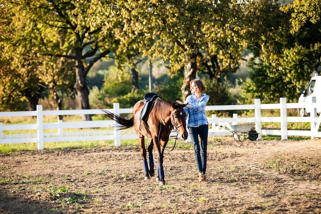 Schönes mädchen, das ihr braunes pferd auf dem bauernhof führt