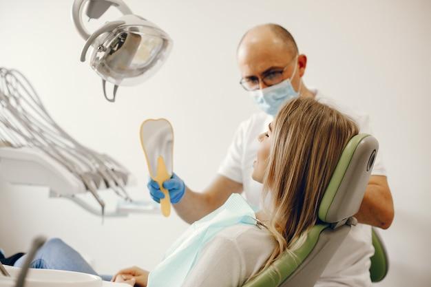 Schönes mädchen, das im büro des zahnarztes sitzt