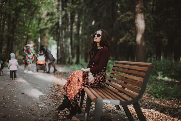 Schönes mädchen, das im herbst auf einer bank im park sitzt