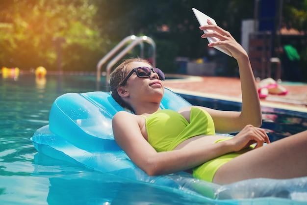 Schönes mädchen, das im pool auf ihren ferien sich entspannt