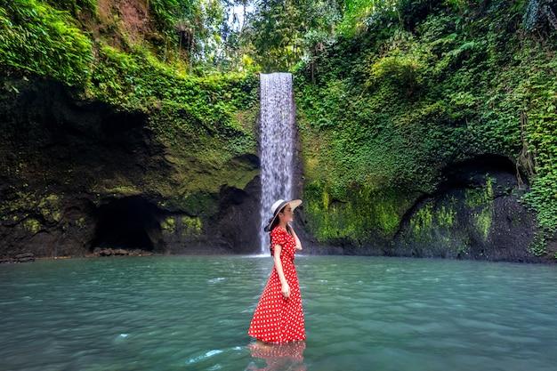 Schönes mädchen, das im tibumana-wasserfall in bali, indonesien steht.