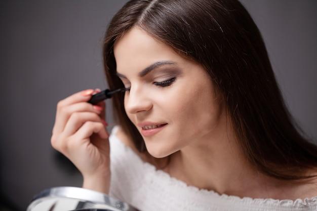 Schönes mädchen, das in den spiegel schaut und kosmetik mit einem großen pinsel anwendet.