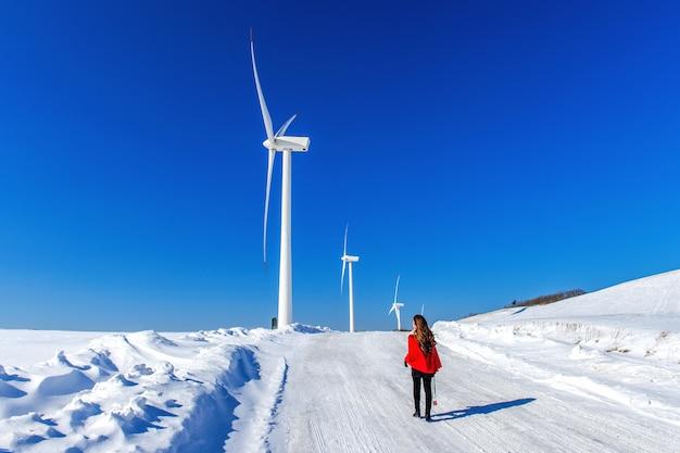 Schönes mädchen, das in der winterlandschaft des himmels und der winterstraße mit schnee und rotem kleid und windkraftanlage geht