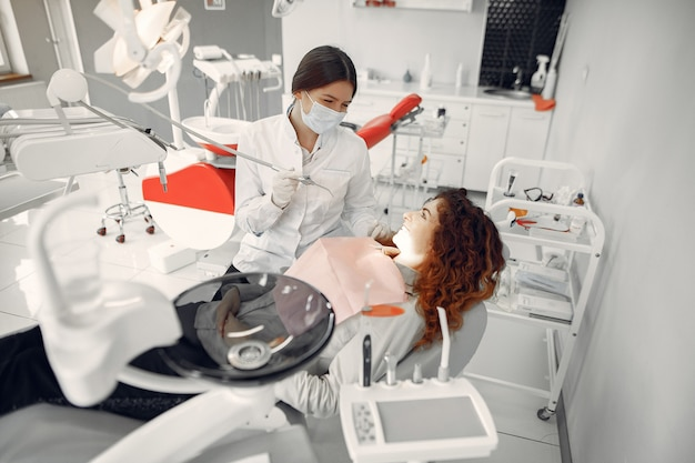 Schönes mädchen, das in der zahnarztpraxis sitzt