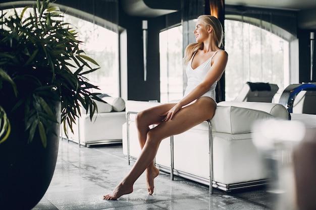 Schönes mädchen, das in einem badekurortsalon sich entspannt