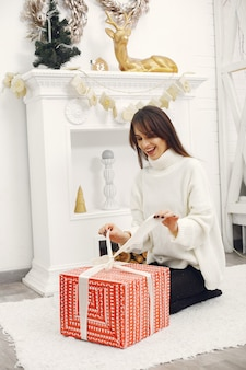 Schönes mädchen, das in einem raum mit weihnachtsgeschenken sitzt