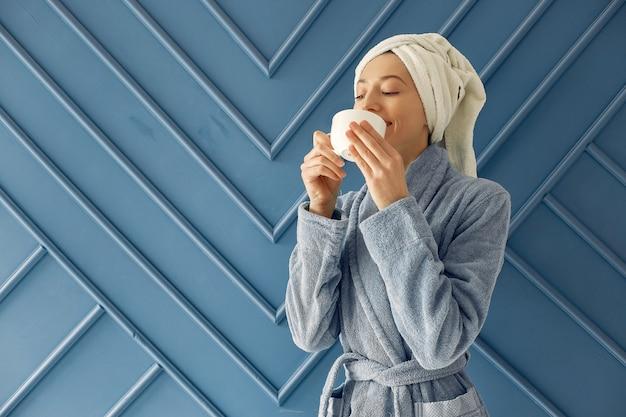 Schönes mädchen, das in einem studio in einem blauen bademantel steht