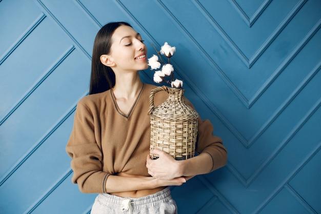 Schönes mädchen, das in einem studio mit baumwollblumen steht