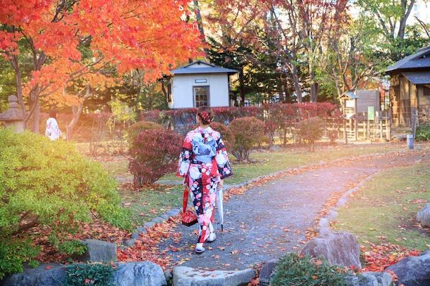 Schönes mädchen, das japanischen traditionellen kimono im herbst trägt.