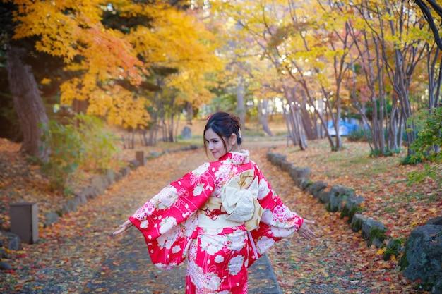 Schönes mädchen, das japanischen traditionellen kimono im herbst trägt