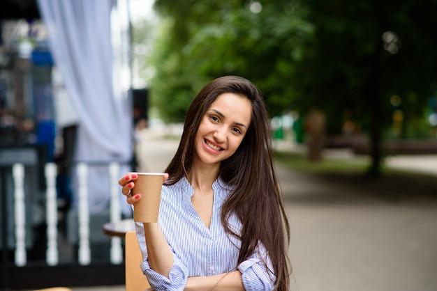 Schönes mädchen, das kaffee lächelt und trinkt.