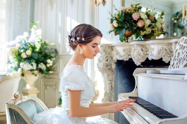 Schönes mädchen, das klavier spielt, in einem schönen kleid im inneren