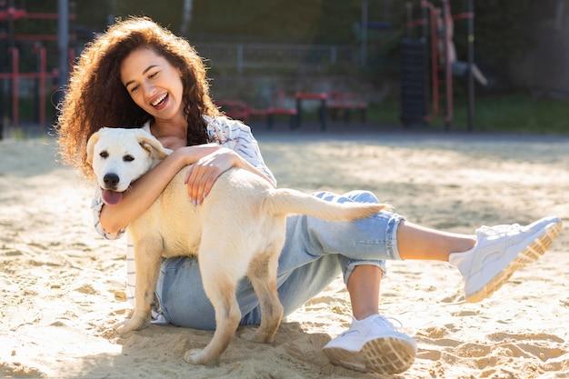 Schönes mädchen, das lächelt, während es ihren hund umarmt
