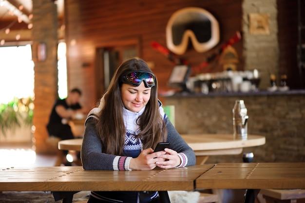 Schönes mädchen, das mit dem telefon in einem café-skigebiet ruht