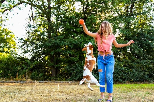 Schönes mädchen, das mit einem beagle-welpen spielt