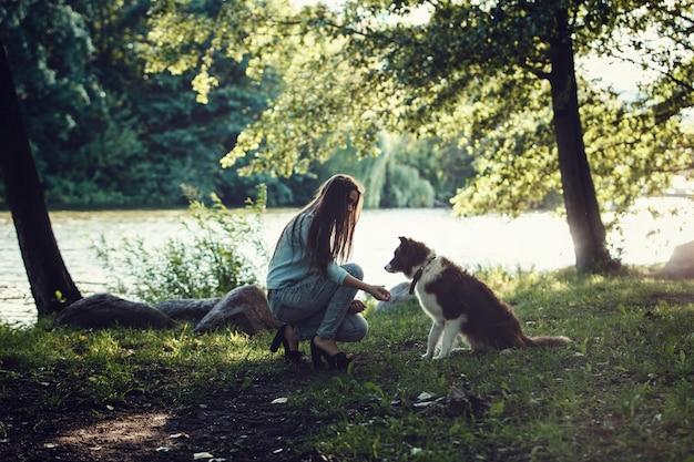 Schönes mädchen, das mit einem hund spielt