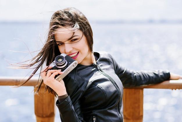 Schönes mädchen, das mit einer alten kamera aufwirft