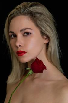 Schönes mädchen, das mit einer roten rose auf einer dunkelheit aufwirft