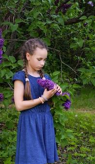 Schönes mädchen, das mit lila blumen in der traurigkeit bleibt