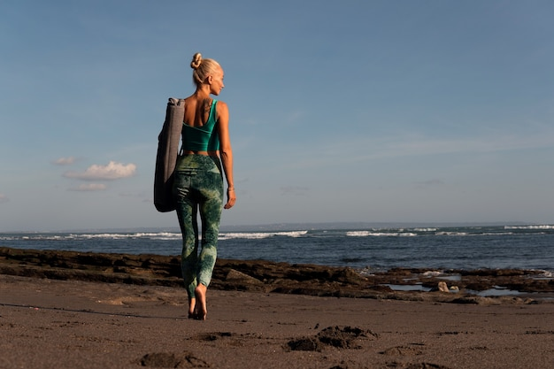 Schönes mädchen, das mit yogamatte am strand spazieren geht