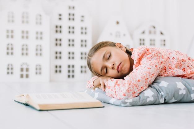 Schönes mädchen, das nach dem lesen schläft