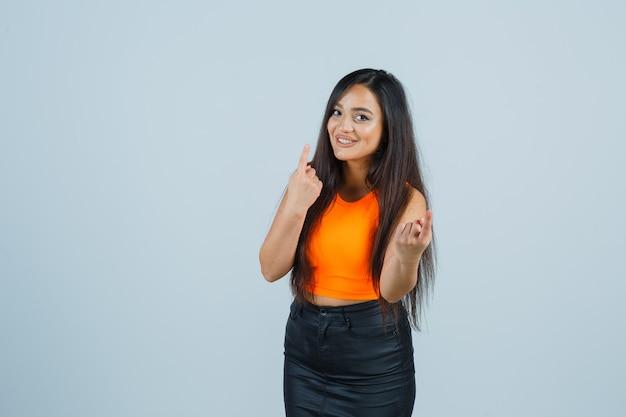 Schönes mädchen, das nummer eins mit finger im orangefarbenen oberteil, rock zeigt und hübsch aussieht, vorderansicht.