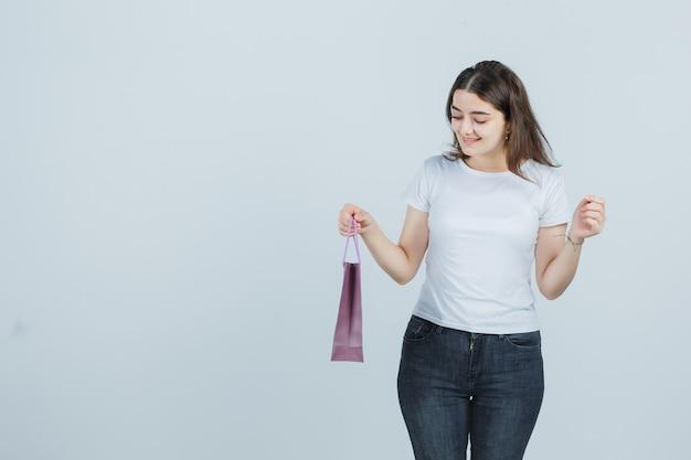 Schönes mädchen, das papiertüte im t-shirt, in den jeans und in der glücklichen vorderansicht hält.