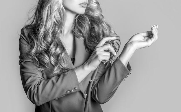 Schönes mädchen, das parfüm verwendet. frau mit einer flasche parfüm. frau präsentiert parfums duft. parfümflasche frau spray aroma. frau, die eine parfümflasche hält schwarz und weiß.