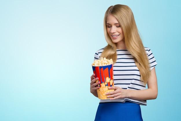Schönes mädchen, das popcorn auf weißem hintergrund isst