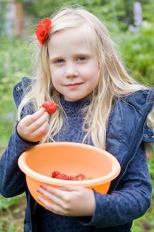 Schönes mädchen, das rote erdbeeren im garten isst