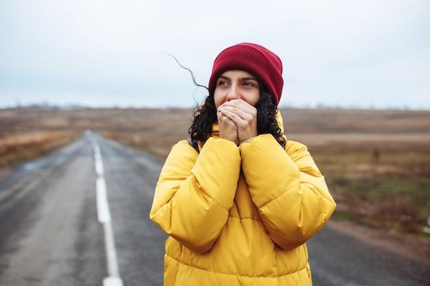Schönes mädchen, das roten hut und gelbe jacke trägt, wärmt ihre hände mit ihrem atem auf der einsamen straße.