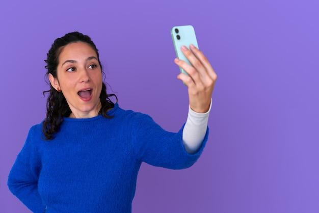 Schönes mädchen, das selfie auf lokalisiertem lila hintergrund trägt, der blauen pullover trägt. smartphone mit einer hand halten, zur kamera lächeln. lockige haare.