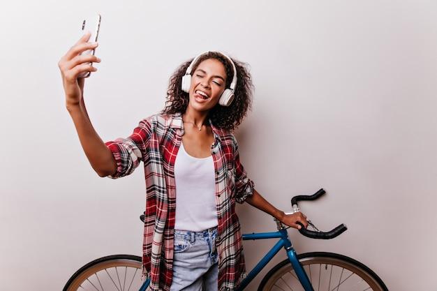 Schönes mädchen, das selfie neben blauem fahrrad macht. studioaufnahme einer hübschen afrikanischen frau, die herumfummelt, während sie sich selbst fotografiert.