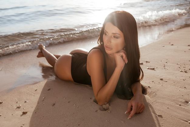 Schönes mädchen, das sich auf einem tropischen sandstrand sonnt. mode junge frau, die auf dem rücken auf sand mit schwarzem badeanzug liegt. gebräunte frau entspannt