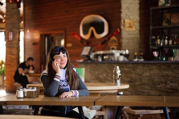 Schönes mädchen, das sich ausruht und am telefon in einem café-skigebiet spricht