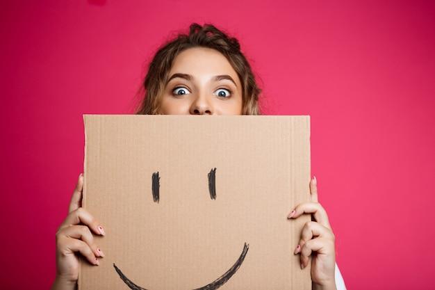 Schönes mädchen, das sich hinter karton mit smiley über rosa wand versteckt.