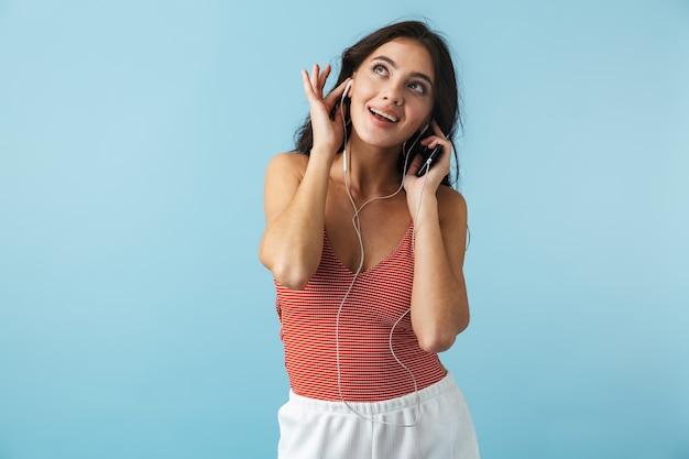 Schönes mädchen, das sommerkleidung trägt, die lokal über blau steht, musik mit kopfhörern hörend, handy haltend