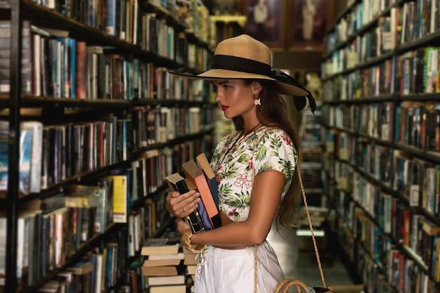 Schönes mädchen, das stilvolles outfit trägt, das nach interessantem buch in der kleinen vintage-buchhandlung sucht